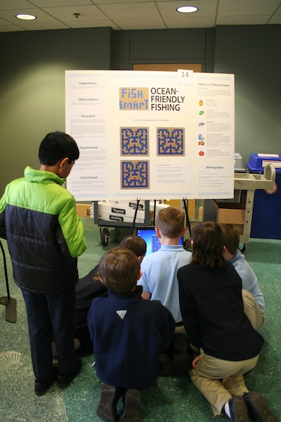 Students surround the one laptop at the science fair.